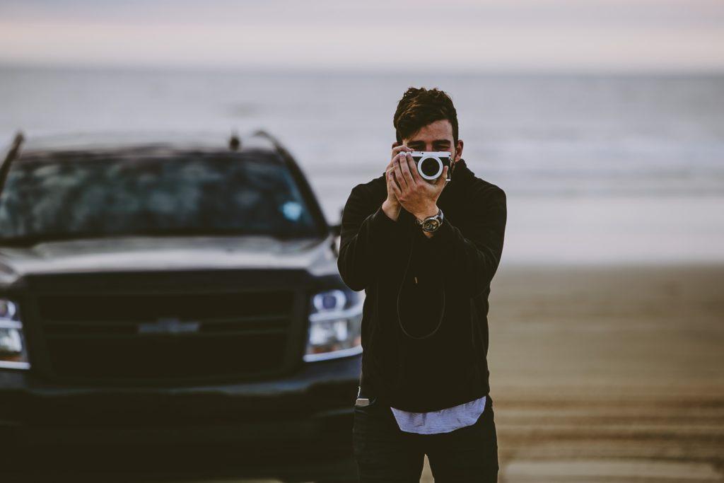 カメラをもつ男性と車