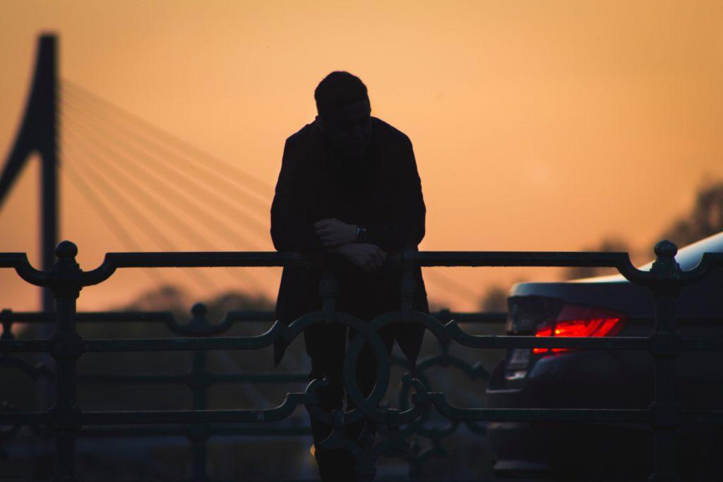 車の近くに腰掛ける男性