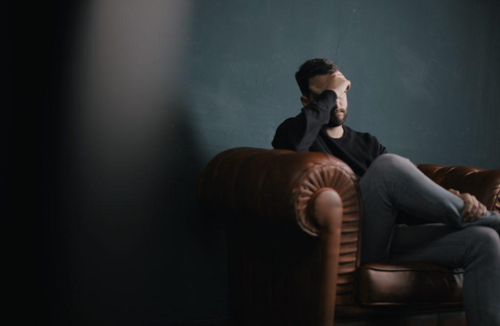 ソファに座って考える男性